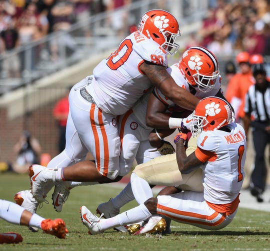 From left, Clemson defensive lineman Dexter Lawrence (90), linebacker Kendall Joseph (34), and cornerback Trayvon Mullen (1) bring down Florida State running back Cam Akers (3) during the 1st quarter Saturday, October 27, 2018 at Florida State's Doak Campbell Stadium in Tallahassee, Fl.