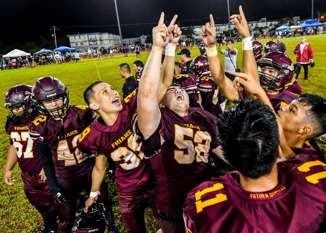 Father Duenas Friars celebrate on the field after winning the Interscholastic Athletic Association of Guam high school football championship game against the George Washington Geckos at the Geckos' field in Mangilao on Saturday, Oct. 27, 2018. The Friars won their 40th straight win and their fourth consecutive title in the league with a final score of 20-14, over the Geckos.