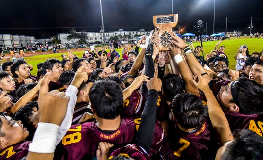 Father Duenas Friars celebrate with their trophy after winning the Interscholastic Athletic Association of Guam high school football championship game against the George Washington Geckos at the Geckos' field in Mangilao on Saturday, Oct. 27, 2018. The Friars won their 40th straight win and their fourth consecutive title in the league with a final score of 20-14, over the Geckos.