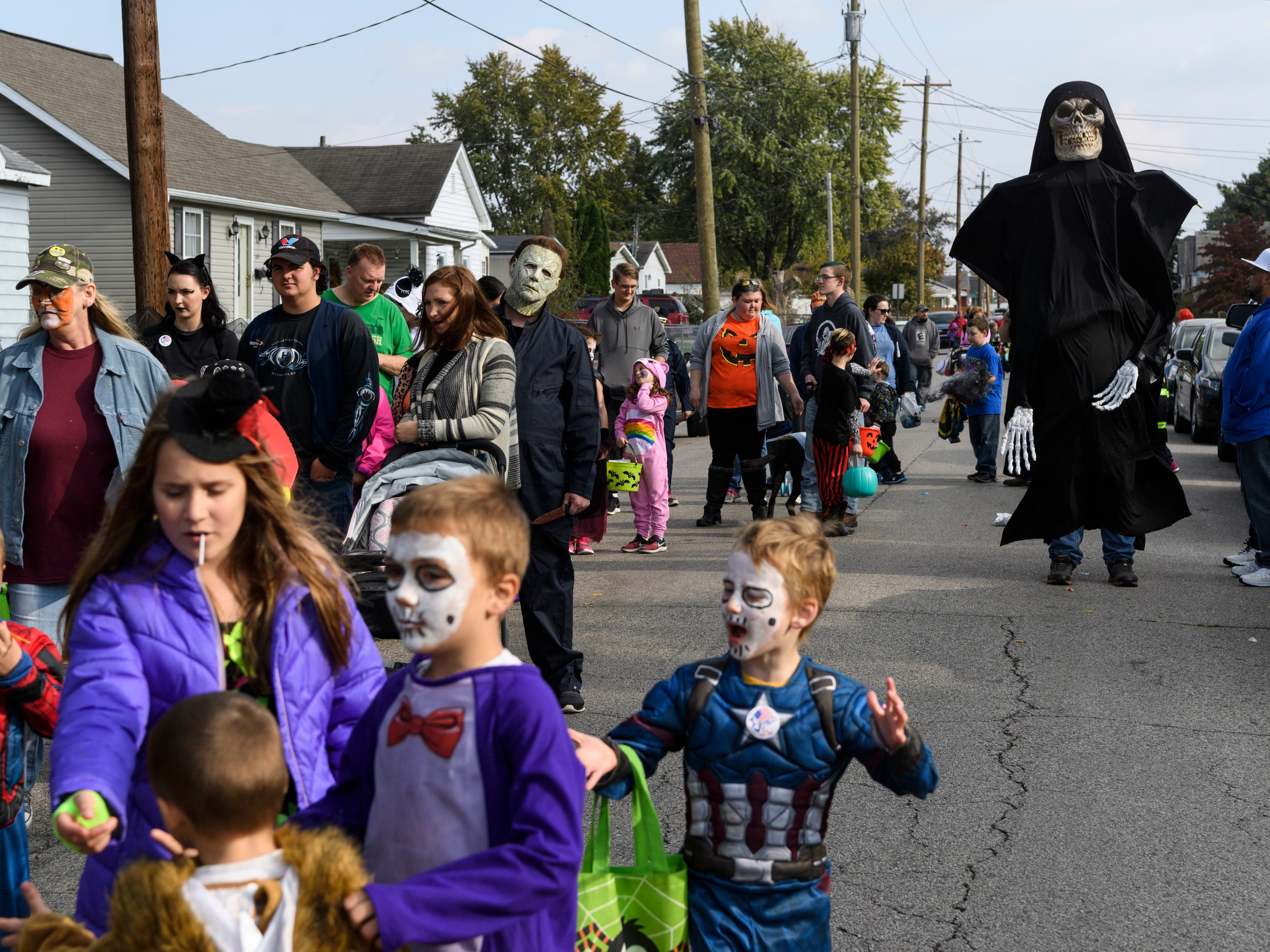 Tim Barron, top right, walks around in spooky skeleton costume during the Halloween Trunk or Treat Extravaganza held along Powell Street in Henderson, Ky., Saturday, Oct. 27, 2018.