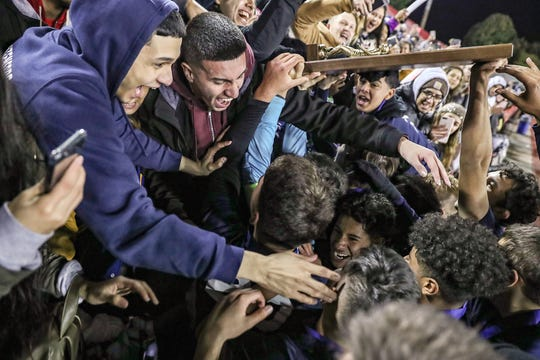 Students celebrate with the Hammond Bishop Noll Warriors after they won IHSAA class 2A state finals at IUPUI's Michael A. Carroll Stadium in Indianapolis, Friday, Oct. 26, 2018. Hammond Bishop Noll defeated Cardinal Ritter, 1-0.
