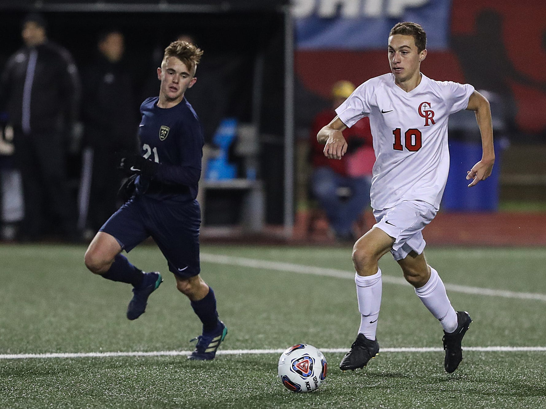 Hammond Bishop Noll Warriors midfielder Noah Reid (21) chases after Cardinal Ritter Raiders midfielder Ryan Hofer (10) during the second half of IHSAA class 2A state finals at IUPUI's Michael A. Carroll Stadium in Indianapolis, Friday, Oct. 26, 2018. Hammond Bishop Noll defeated Cardinal Ritter, 1-0.