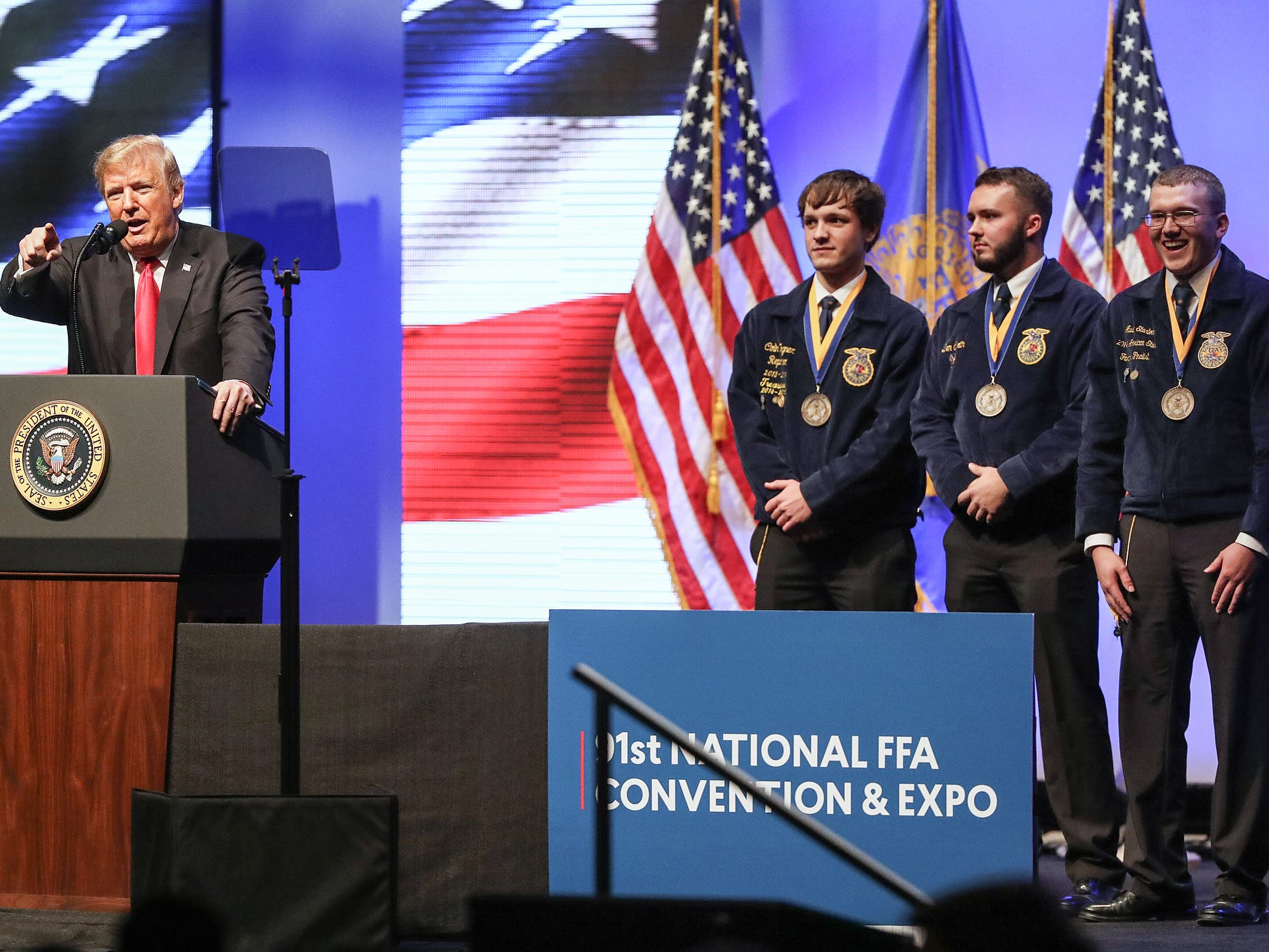 President Donald Trump recognizes FFA award recipients Colin Wegner, Benjamin Curtain and Austin Stanton during his speech at the annual Future Farmers of America Convention and Expo at Banker's Life Fieldhouse in Indianapolis, Saturday, Oct. 27, 2018.