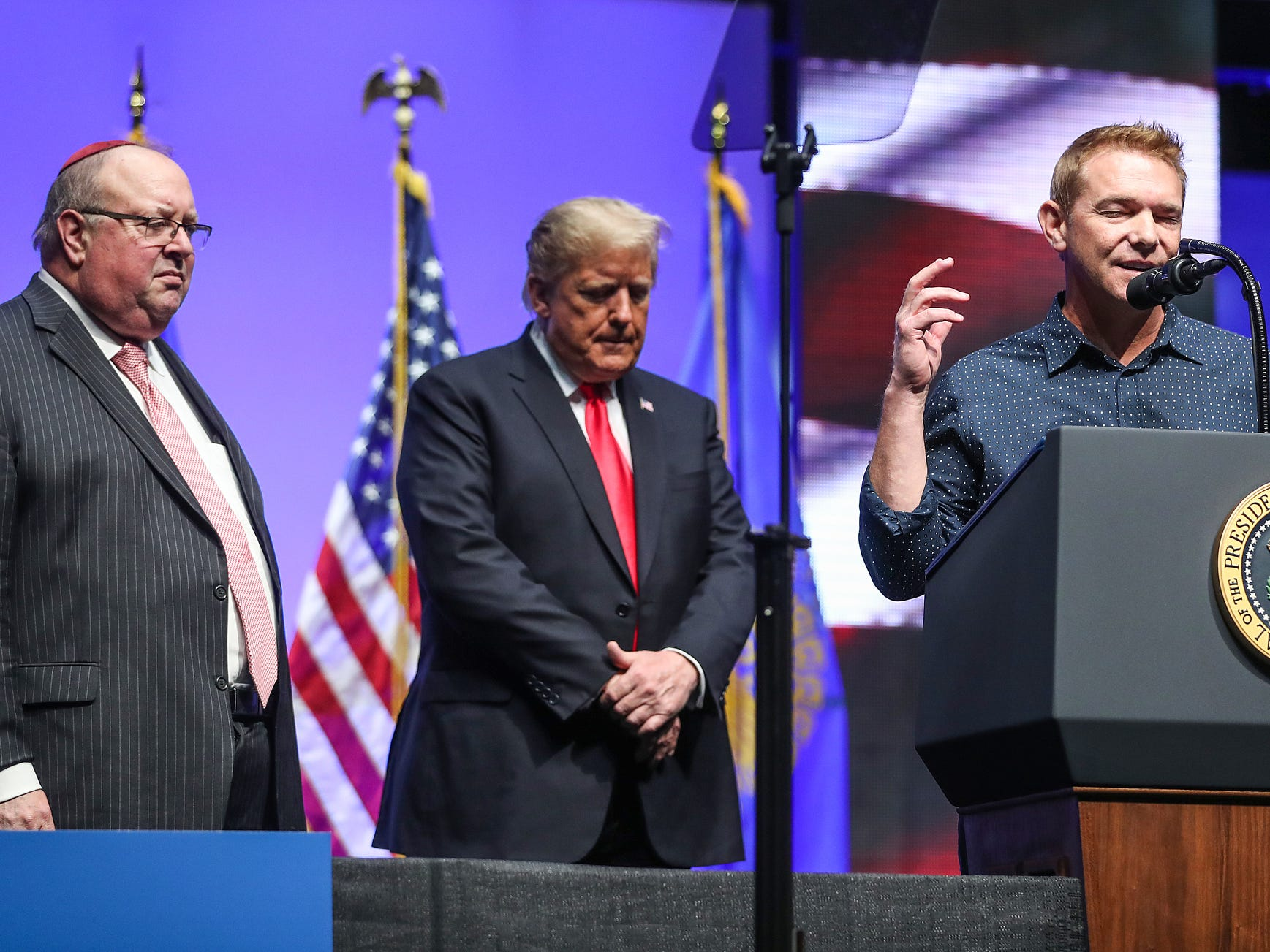 United States President Donald Trump brought local Rabbi Benjamin Sendrow, left, and Pastor Thom O'Leary, right, onstage to say prayers in light of the morning's synagogue shooting in Pittsburgh, during his speech at the annual Future Farmers of America Convention and Expo at Banker's Life Fieldhouse in Indianapolis, Saturday, Oct. 27, 2018.