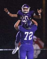 Brownsburg High School junior Donny Marcus (20) his hoisted into the air by senior teammate Jason Meeks (72) after scoring a touchdown during the first half of action. Brownsburg High School hosted Southport High School in the 2018-19 IHSAA Football State Tournament Class 6A first-round sectional game Friday, Oct. 26, 2018.