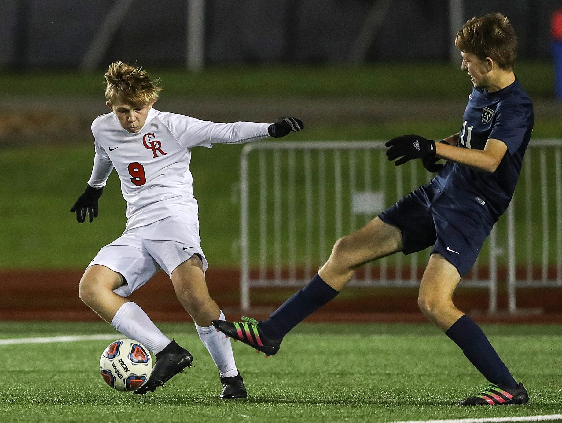 Cardinal Ritter Raiders midfielder Jason Hofer (9) keeps the ball away from Hammond Bishop Noll Warriors midfielder Henry Smith (11) during the second half of IHSAA class 2A state finals at IUPUI's Michael A. Carroll Stadium in Indianapolis, Friday, Oct. 26, 2018. Hammond Bishop Noll defeated Cardinal Ritter, 1-0.
