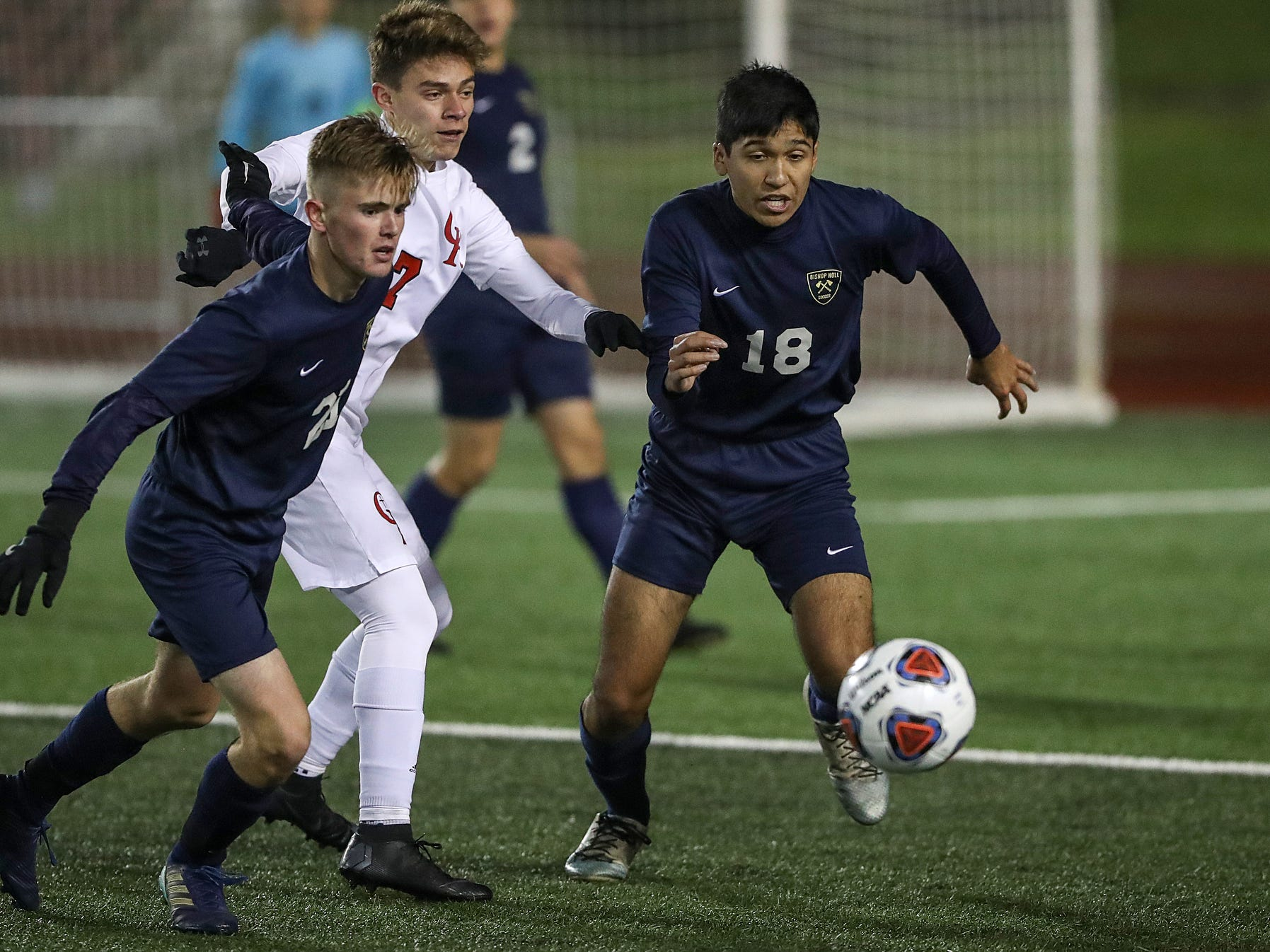 Cardinal Ritter Raiders midfielder Andy Bonilla (7) breaks between Hammond Bishop Noll Warriors Noah Reid (21) and Brandon Fuentes (18) during the first half of IHSAA class 2A state finals at IUPUI's Michael A. Carroll Stadium in Indianapolis, Friday, Oct. 26, 2018. Hammond Bishop Noll defeated Cardinal Ritter, 1-0.