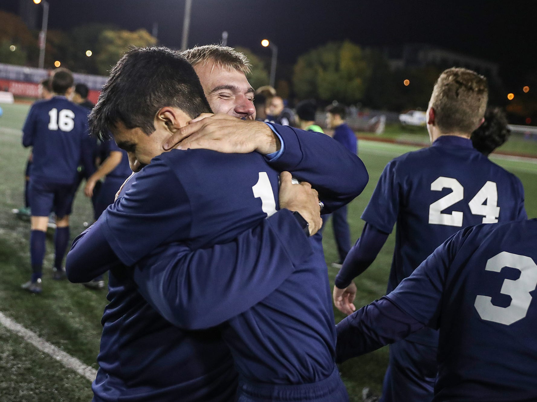 Hammond Bishop Noll Warriors Brandon Fuentes (18) celebrates with a coach after the Warriors won IHSAA class 2A state finals at IUPUI's Michael A. Carroll Stadium in Indianapolis, Friday, Oct. 26, 2018. Hammond Bishop Noll defeated Cardinal Ritter, 1-0.
