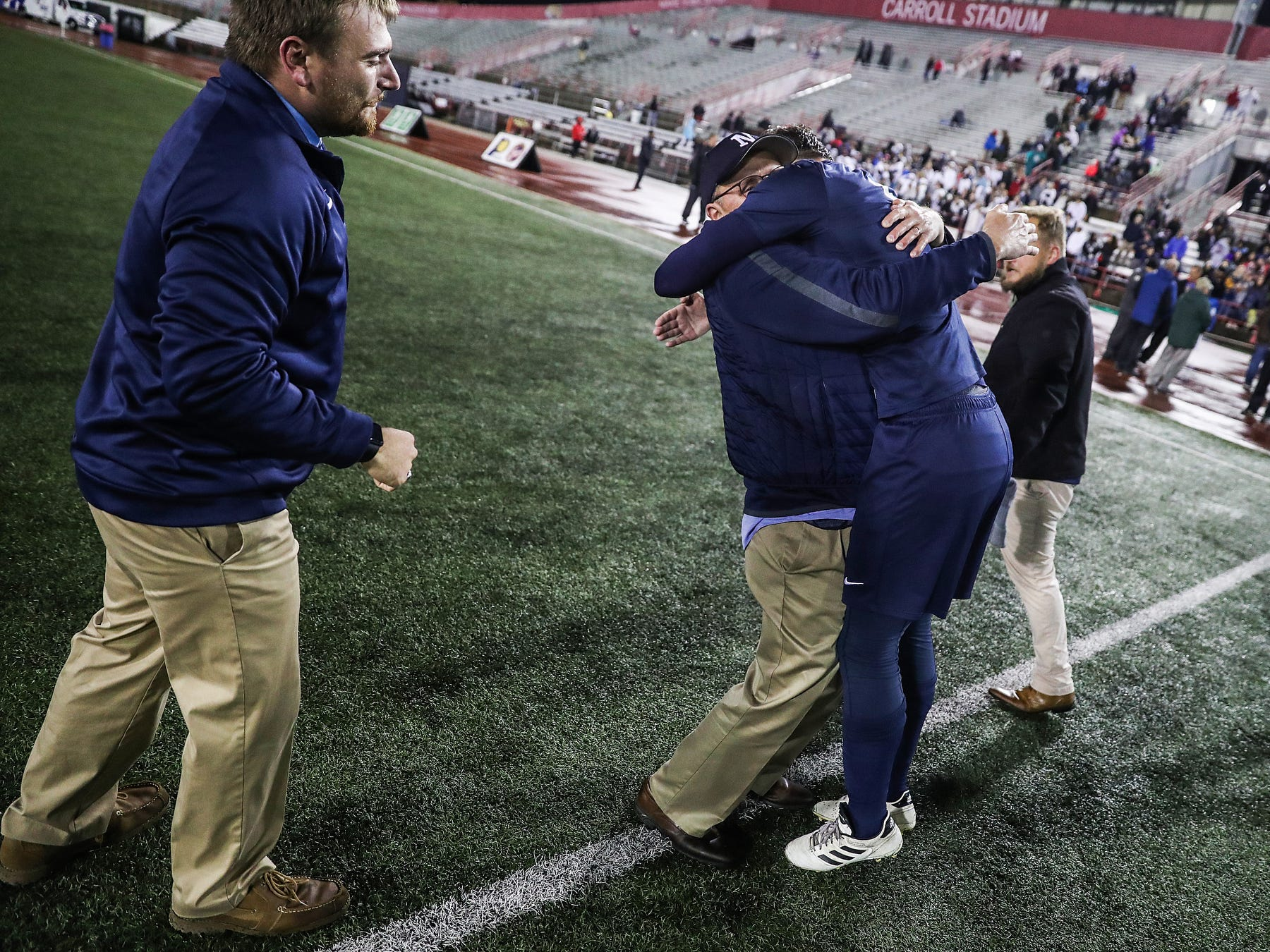 A Hammond Bishop Noll player celebrates with a coach after the Warriors won IHSAA class 2A state finals at IUPUI's Michael A. Carroll Stadium in Indianapolis, Friday, Oct. 26, 2018. Hammond Bishop Noll defeated Cardinal Ritter, 1-0.