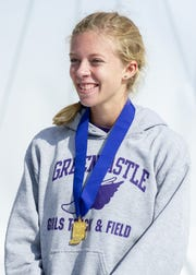 Greencastle High School runner Emma Wilson smiles after being awarded the first-place medal after the running of the IHSAA Boys' and Girls' Cross Country State Finals meet on Saturday.