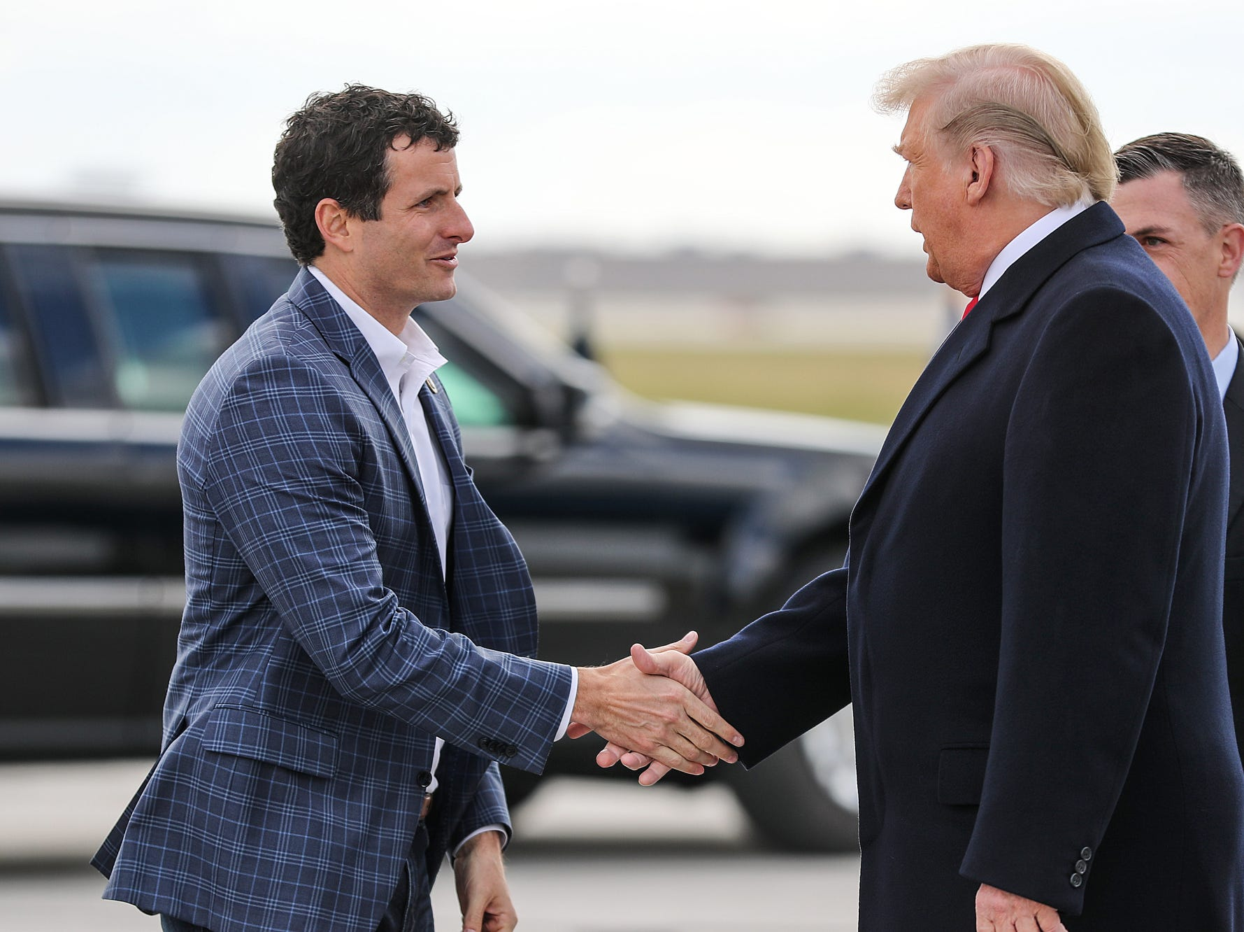 United States President Donald Trump greets Congressman Trey Hollingsworth on the tarmac at Indianapolis International Airport, where he arrived to speak at the annual Future Farmers of America Convention and Expo at Banker's Life Fieldhouse, Saturday, Oct. 27, 2018.