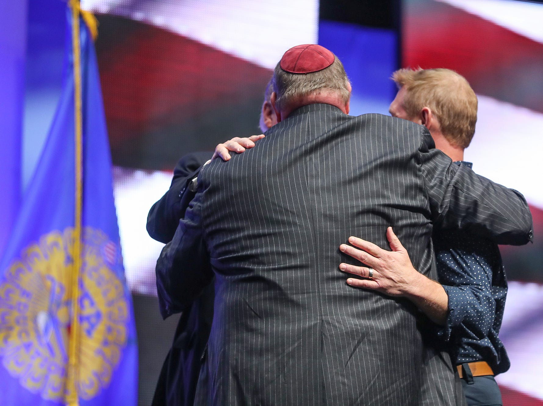 United States President Donald Trump shares a hug with Rabbi Benjamin Sendrow and Pastor Thom O'Leary, who he brought onstage to say prayers during his speech at the annual Future Farmers of America Convention and Expo at Banker's Life Fieldhouse in Indianapolis, Saturday, Oct. 27, 2018.