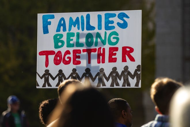 """A person holds a sign reading """"Families Belong Together"""" during the """"Rally for Immigration Reform"""" on Saturday, Oct. 27, 2018, on the east side the Pentacrest in Iowa City."""
