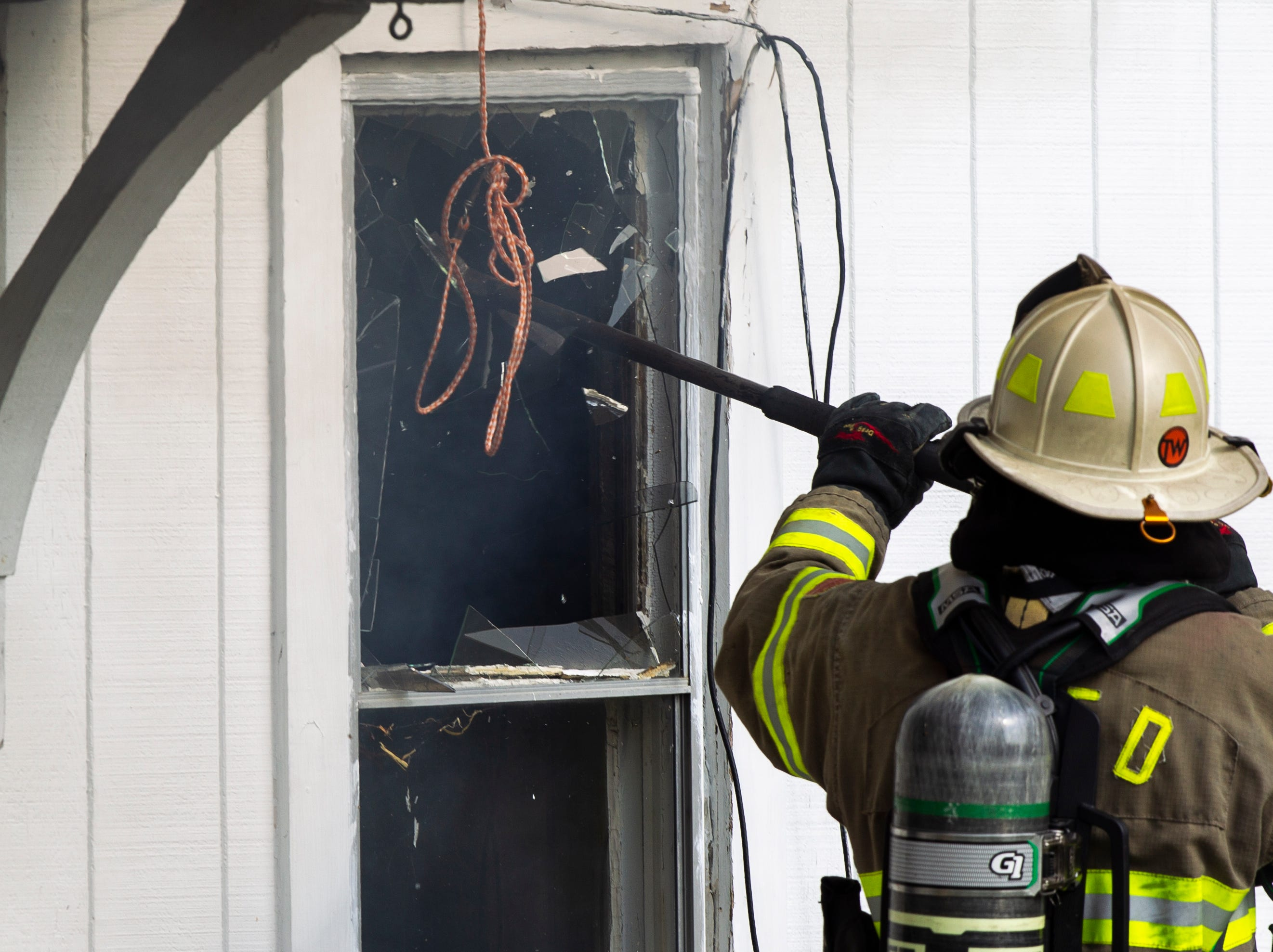Chris Kochanny of the North Liberty Fire Department breaks out a window during controlled burn fire training exercise of a farm house on Saturday, Oct. 27, 2018, on the east side of Liberty High School in North Liberty.