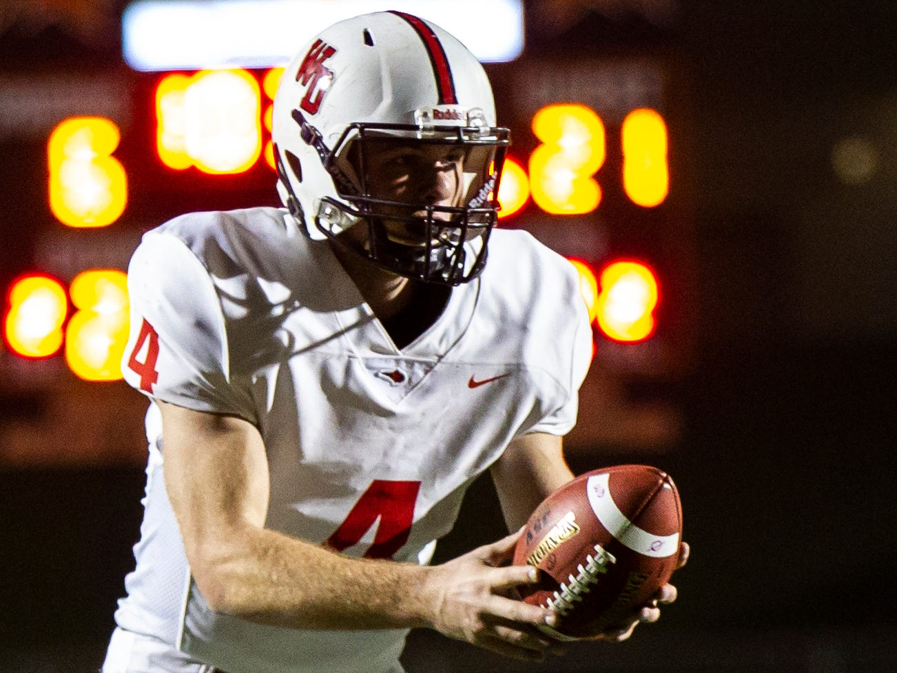 Western Dubuque's Calvin Harris (4) hands the ball off during a Class 3A varsity first round playoff football game on Friday, Oct. 26, 2018, at Spartan Stadium in Solon, Iowa.
