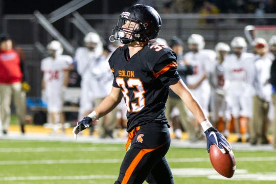 Solon's Clay Gerdin (33) walks with the ball in hand after scoring a touchdown during a Class 3A varsity first round playoff football game on Friday, Oct. 26, 2018, at Spartan Stadium in Solon, Iowa.