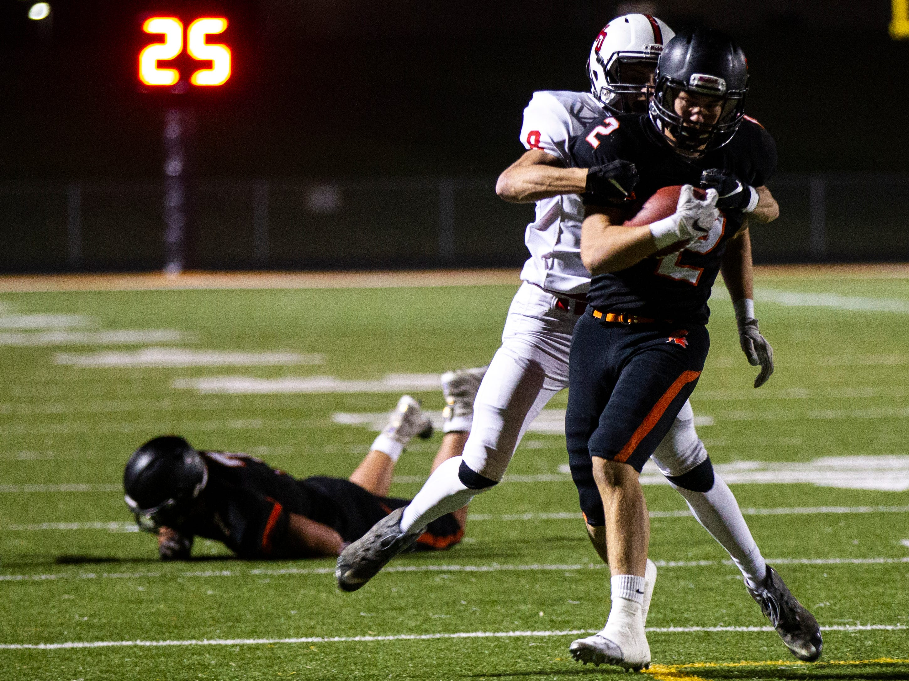 Solon's Seamus Poynton (2) pulls in a reception past Western Dubuque's Sam Goodman (8) during a Class 3A varsity first round playoff football game on Friday, Oct. 26, 2018, at Spartan Stadium in Solon, Iowa.