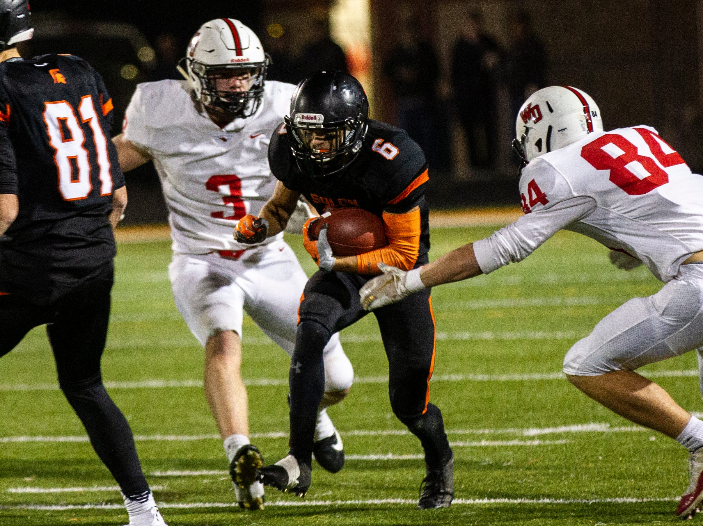 Solon's Dillon Holt (6) finds a hole between Western Dubuque's Jason Simon-Ressler (3) and Bryce Ploessl (84) during a Class 3A varsity first round playoff football game on Friday, Oct. 26, 2018, at Spartan Stadium in Solon, Iowa.