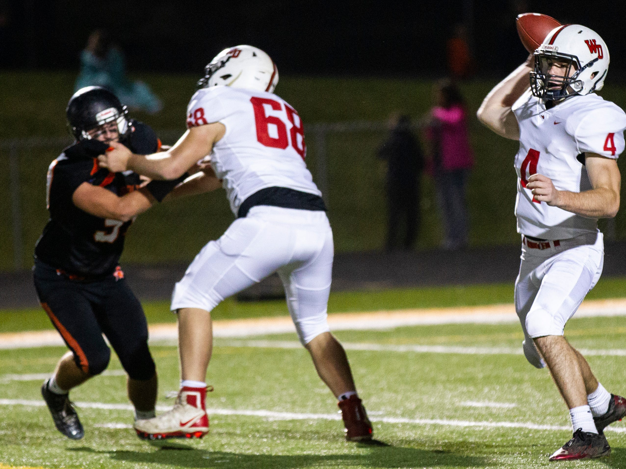 Western Dubuque's Calvin Harris (4) passes while Tim Althaus (68) protects the pocket during a Class 3A varsity first round playoff football game on Friday, Oct. 26, 2018, at Spartan Stadium in Solon, Iowa.