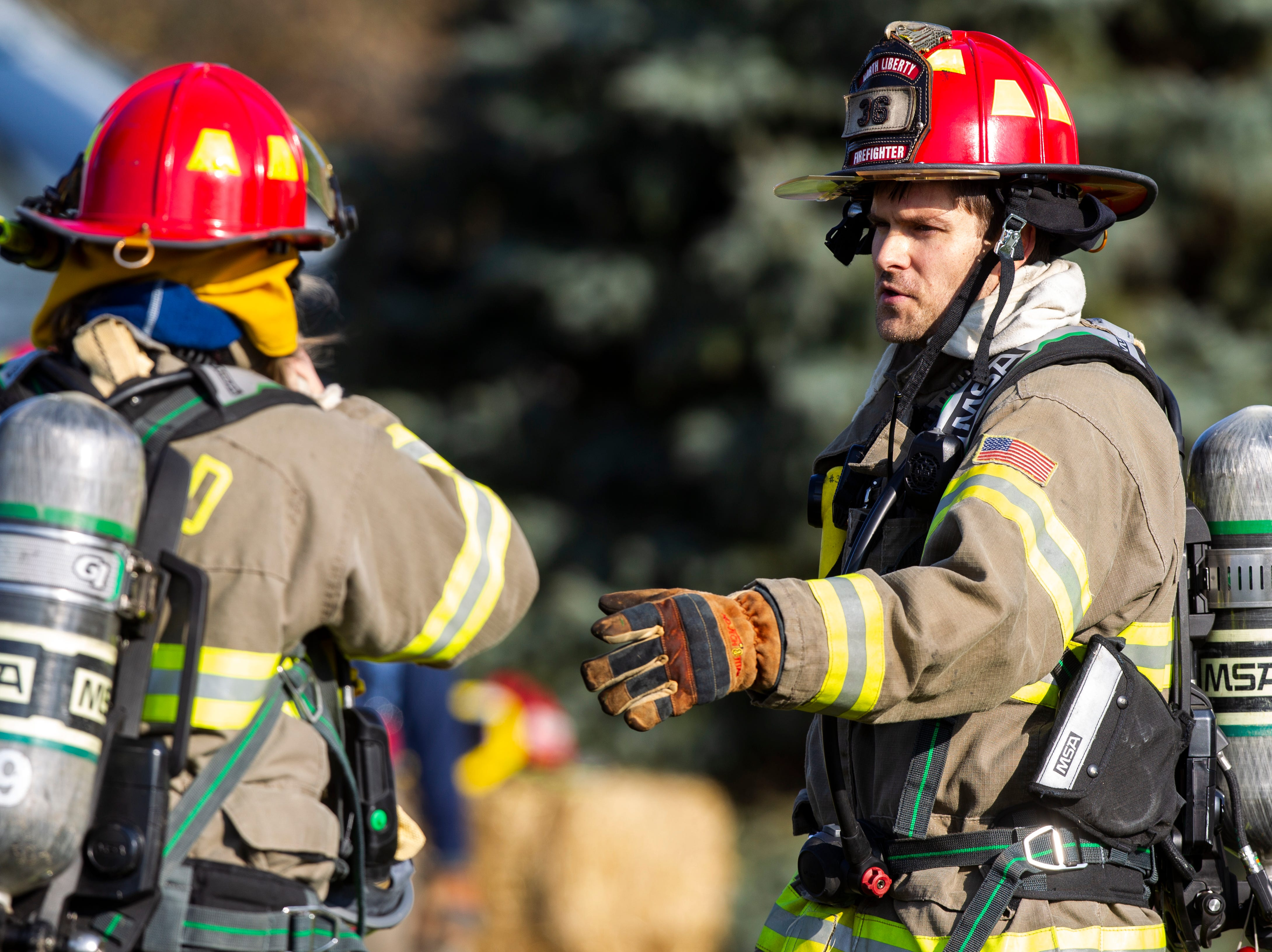 North Liberty Fire Department volunteer firefighter Richard Reasner (right) helps conduct a controlled burn fire training exercise of a farm house on Saturday, Oct. 27, 2018, on the east side of Liberty High School in North Liberty.