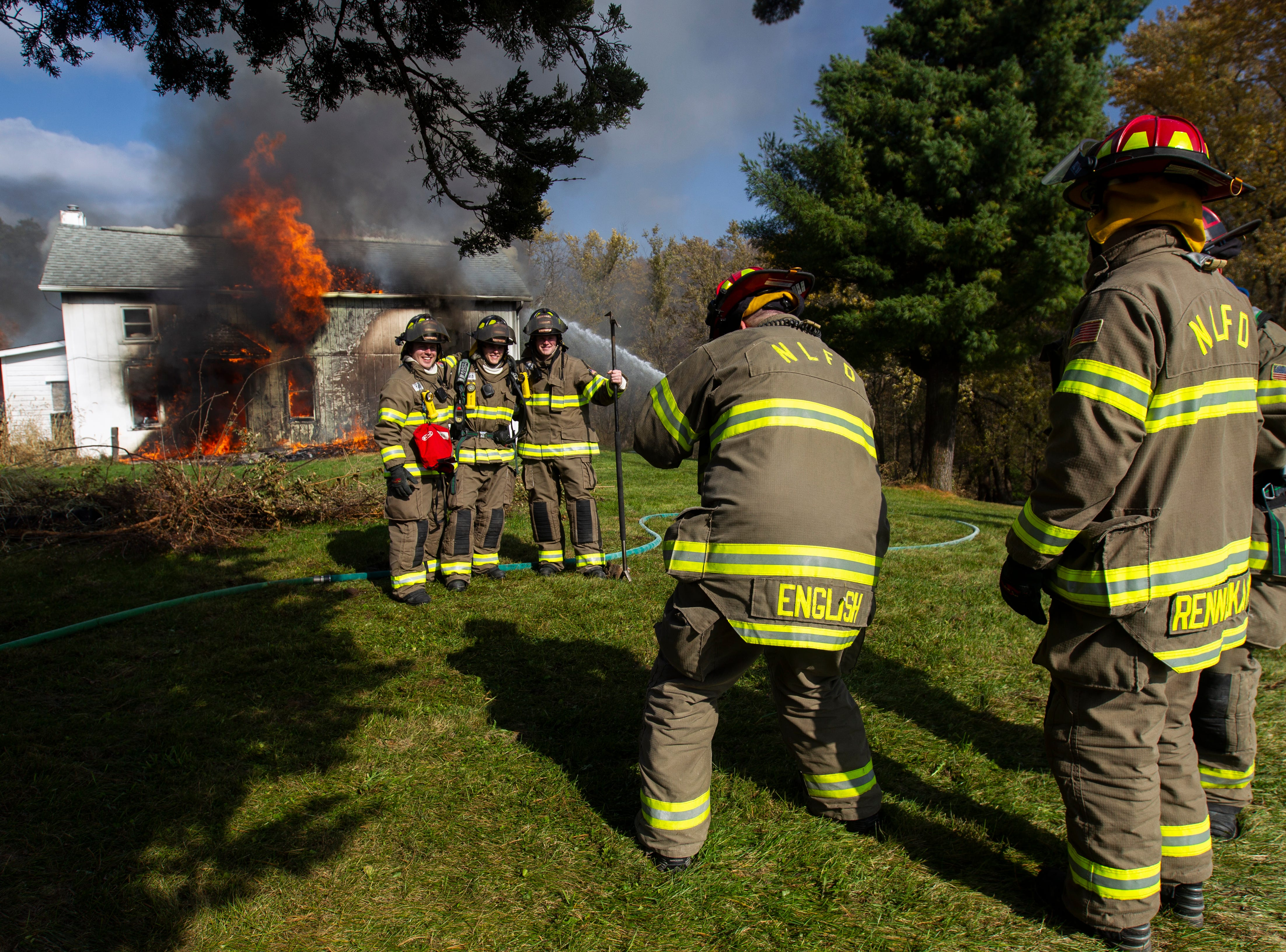 North Liberty Fire Department volunteer Joseph English takes a photo during a controlled burn fire training exercise of a farm house on Saturday, Oct. 27, 2018, on the east side of Liberty High School in North Liberty.