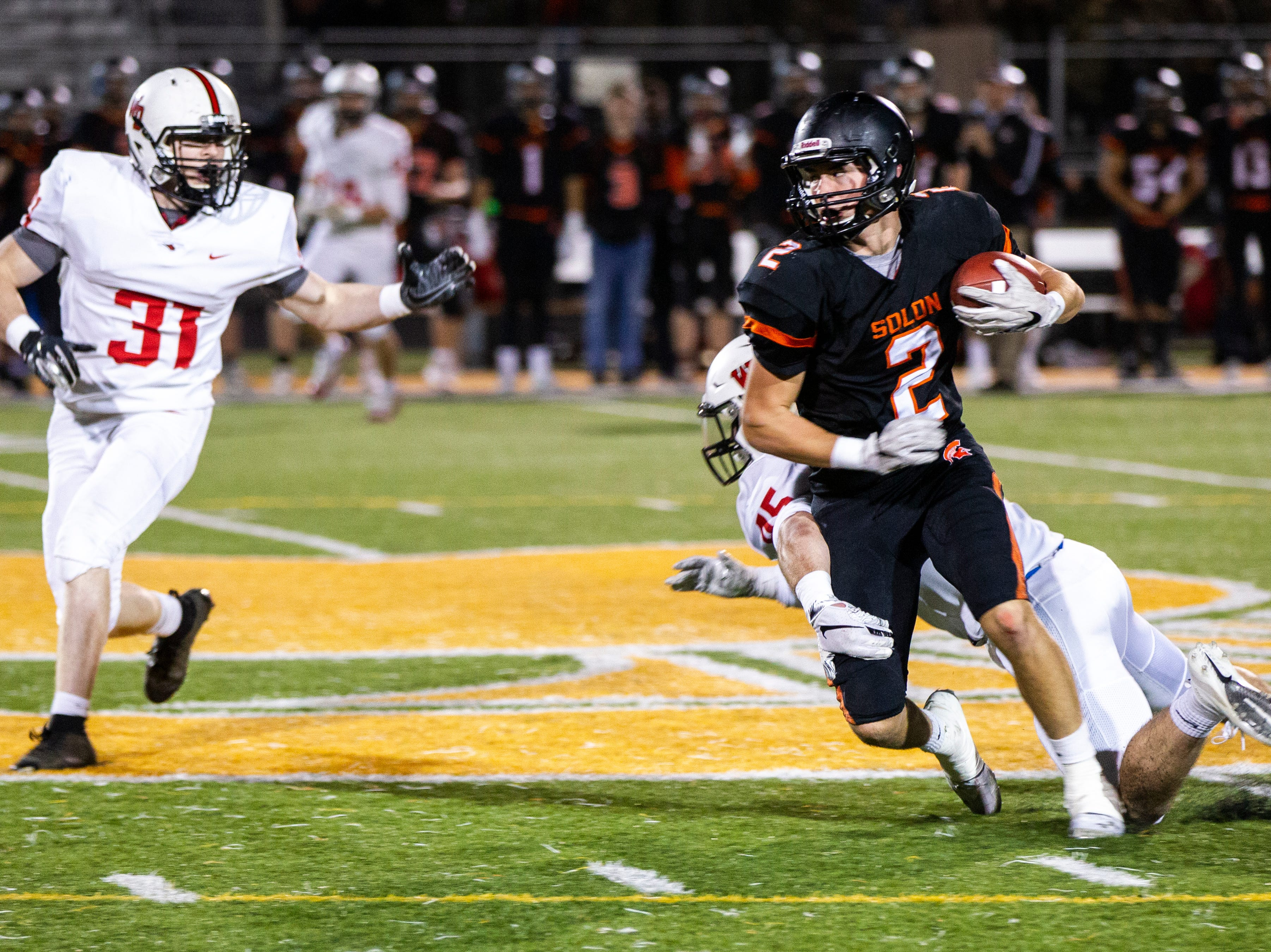 Solon's Seamus Poynton (2) pulls in a pass while crossing midfield during a Class 3A varsity first round playoff football game on Friday, Oct. 26, 2018, at Spartan Stadium in Solon, Iowa.