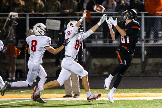 Solon's A.J. Coons pulls in a pass while being covered by Western Dubuque's Sam Goodman (8) and Bryce Ploessl (84) during a Class 3A varsity first round playoff football game on Friday, Oct. 26, 2018, at Spartan Stadium in Solon, Iowa.
