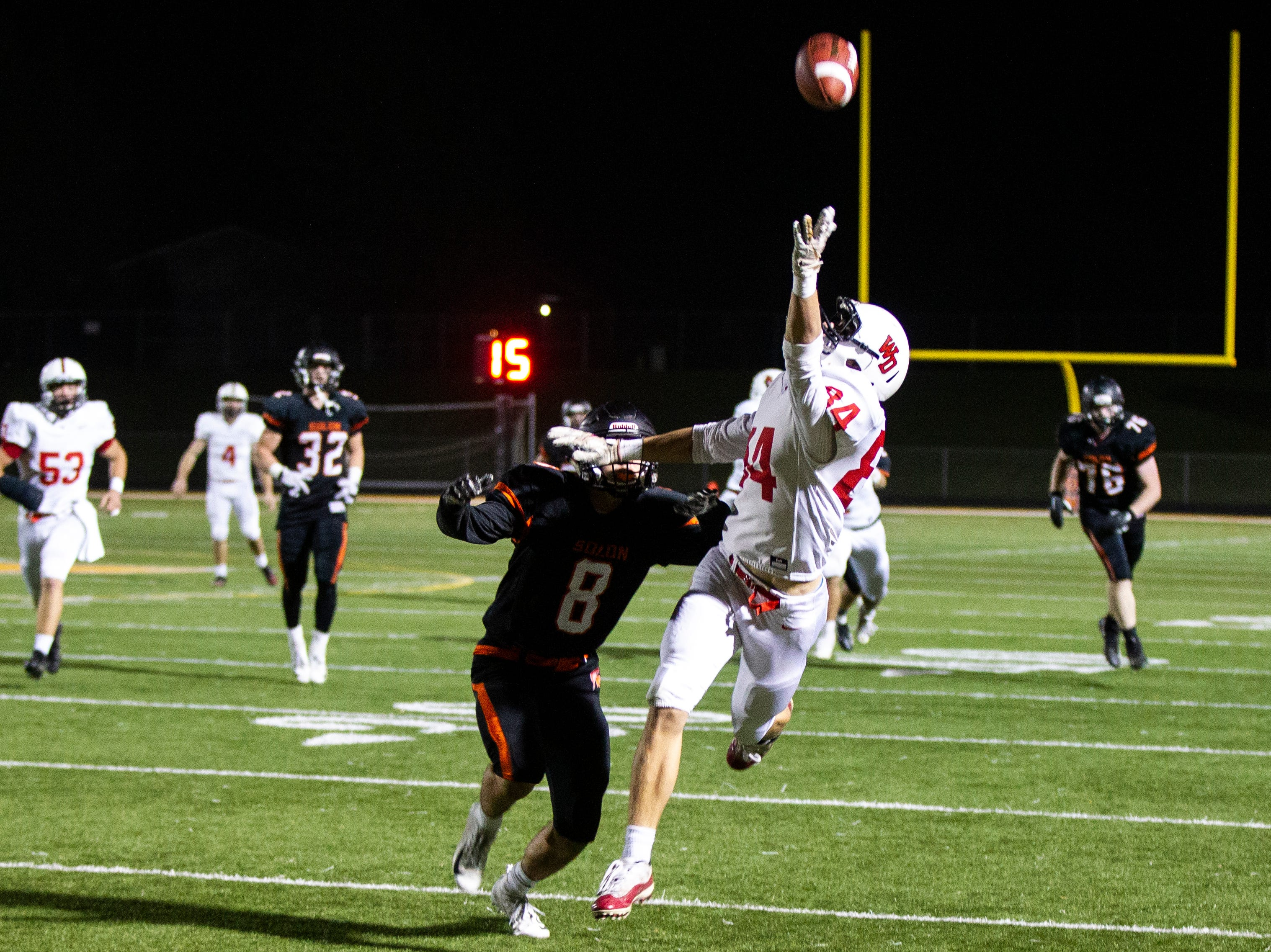 Western Dubuque's Drake George (34) reaches for a ball while being covered by Solon's Jackson Pipolo (8) during a Class 3A varsity first round playoff football game on Friday, Oct. 26, 2018, at Spartan Stadium in Solon, Iowa.