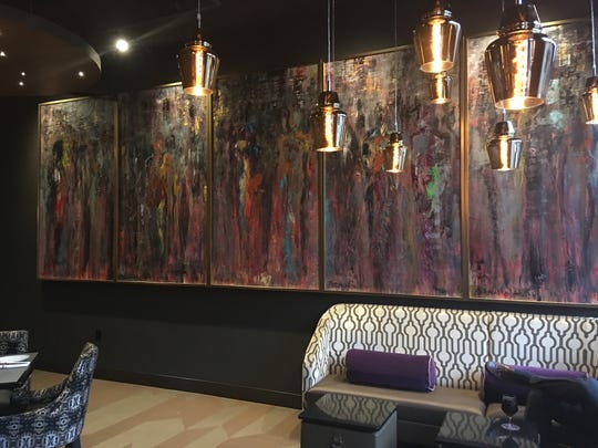 Artwork by Mark Carson English lines one wall of the dining area of Kefi restaurant.