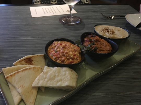 A sampling of three spreads at Kefi restaurant includes left to right, spicy feta cheese, muhammara, and warm butter and toasted pine nut hummus.