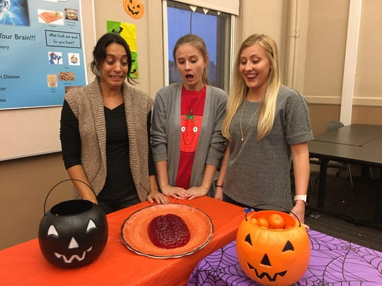 Liat Koenig, left, is studying to be a nutritionist at UT, which is pretty scary considering that's a brain she's serving to guests. Equally appalled are seniors Veronika Vafina and Rachel Mullen. Oct. 26, 2018.