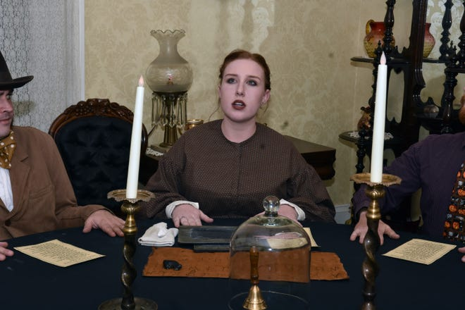 Madame Blavatsky, played by actress Emma Wright, calls for a spirit to communicate with her during the seance experience at Mabry-Hazen House on Friday, Oct. 26.