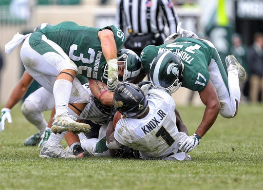 Oct 27, 2018; East Lansing, MI, USA; Purdue Boilermakers running back D.J. Knox (1) is tackled by Michigan State Spartans linebacker Joe Bachie (35) and linebacker Tyriq Thompson (17) during the second half at Spartan Stadium. Mandatory Credit: Mike Carter-USA TODAY Sports