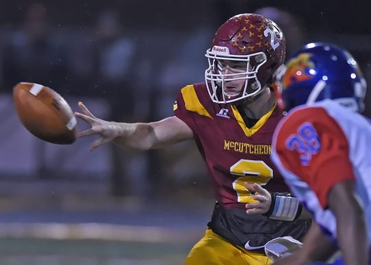 Senior McCutcheon QB Peyton Williams pitches the ball out of the pocket under pressure from Kokomo's DeShawn Winston.