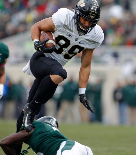 Purdue's Brycen Hopkins leaps over Michigan State's David Dowell on a pass reception during the first quarter of an NCAA college football game, Saturday, Oct. 27, 2018, in East Lansing, Mich. (AP Photo/Al Goldis)