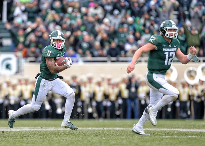 Oct 27, 2018; East Lansing, MI, USA; Michigan State Spartans wide receiver Jalen Nailor (8) is lead into the end zone by Michigan State Spartans quarterback Rocky Lombardi (12) during the second half of a game at Spartan Stadium. Mandatory Credit: Mike Carter-USA TODAY Sports