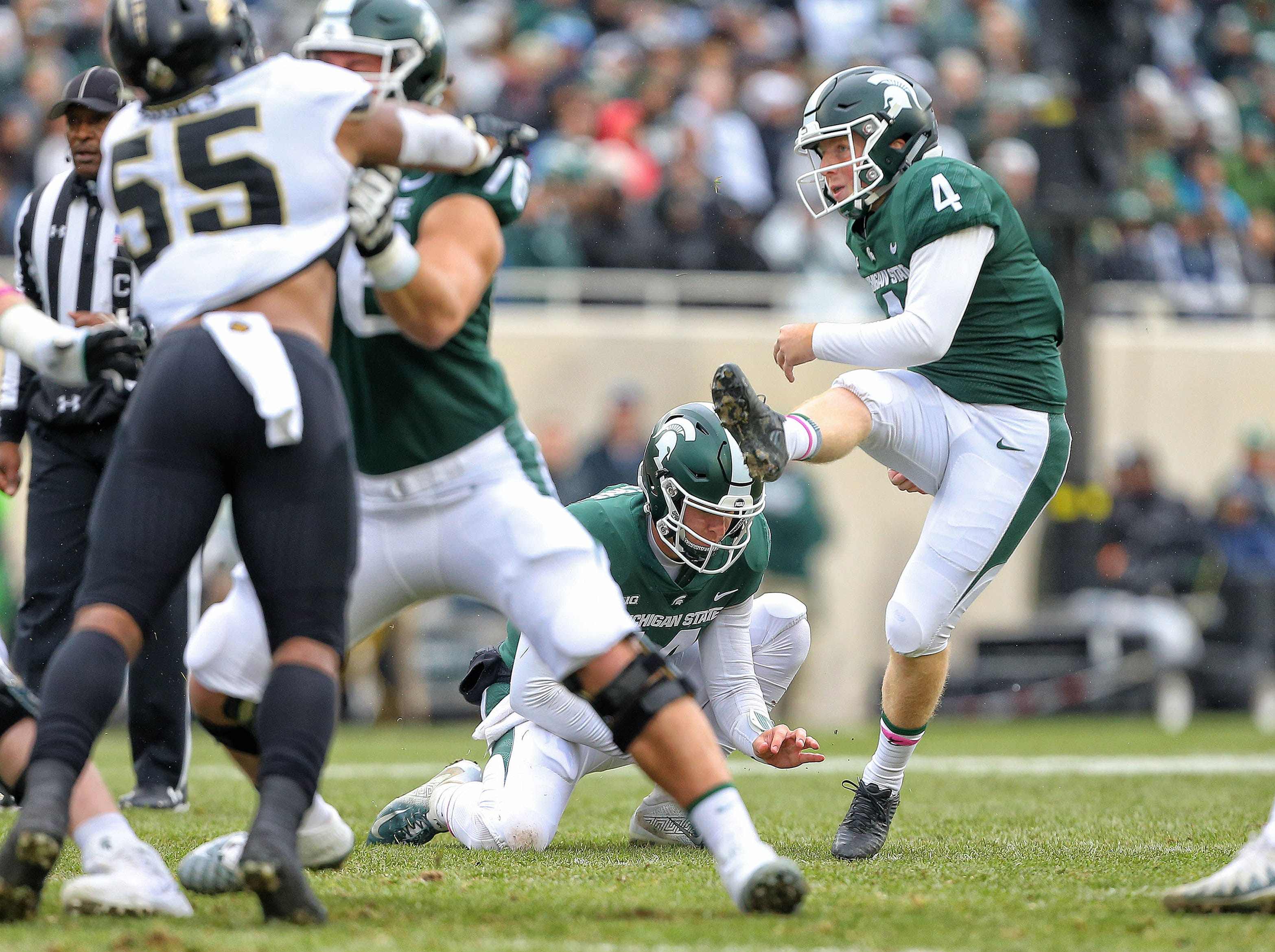 Oct 27, 2018; East Lansing, MI, USA; Michigan State Spartans place kicker Matt Coghlin (4) kicks a field goal out of the hold of Michigan State Spartans quarterback Brian Lewerke (14) during the first quarter of a game at Spartan Stadium. Mandatory Credit: Mike Carter-USA TODAY Sports