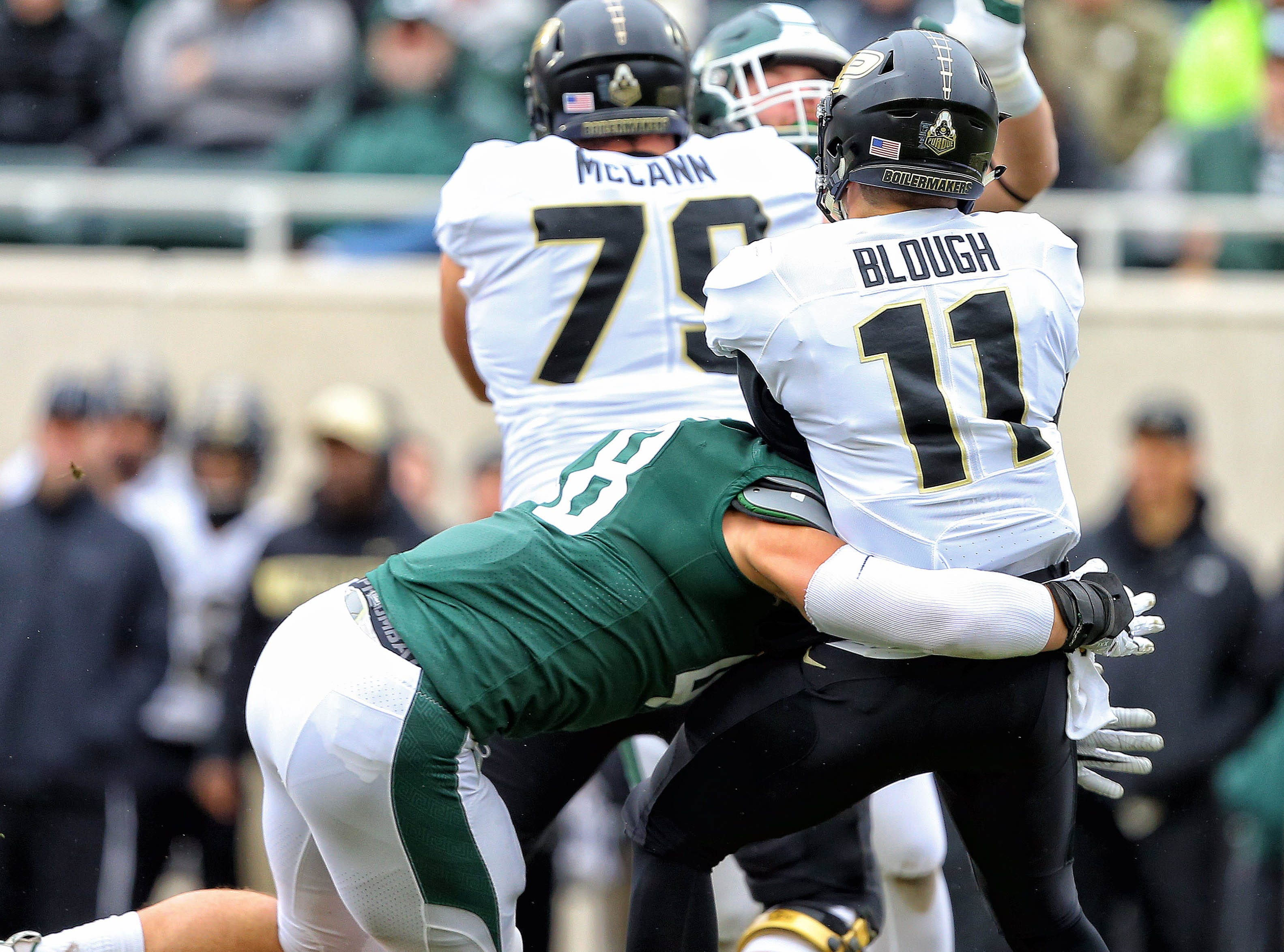 Oct 27, 2018; East Lansing, MI, USA; Purdue Boilermakers quarterback David Blough (11) is sacked by Michigan State Spartans defensive end Kenny Willekes (48) during the first quarter of a game at Spartan Stadium. Mandatory Credit: Mike Carter-USA TODAY Sports