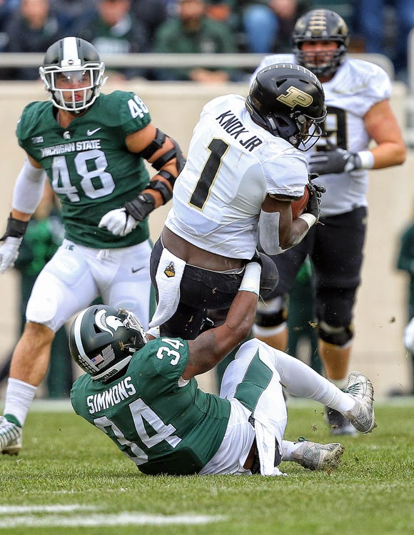 Oct 27, 2018; East Lansing, MI, USA; Purdue Boilermakers running back D.J. Knox (1) is tackled by Michigan State Spartans linebacker Antjuan Simmons (34) during the first quarter of a game at Spartan Stadium. Mandatory Credit: Mike Carter-USA TODAY Sports