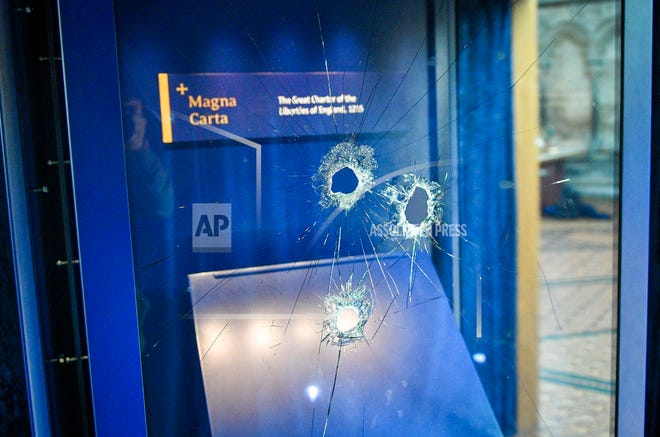 Hammer holes in the glass case that housed the Magna Carta, at Salisbury Cathedral after a 45-year-old man has been arrested on suspicion of its attempted theft, in Salisbury, England, Friday Oct. 26, 2018. British police said Friday that cathedral alarms sounded Thursday when a person tried to smash the glass display box surrounding the Magna Carta in Salisbury Cathedral, and a man has been arrested.