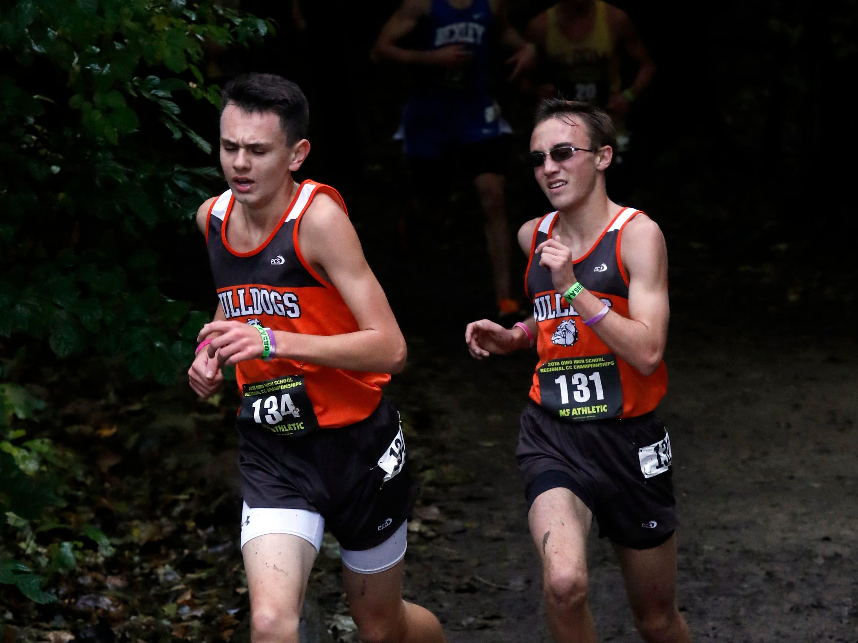Heath's Jack Lutz, left, and Paul Collier run in the Regional Cross Country meet Saturday, Oct. 27, 2018, at Pickerington North High School in Pickerington.