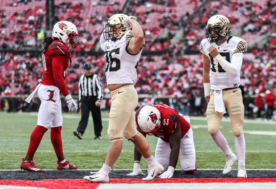 Wake Forest's Cade Carney flexes after scoring a touchdown against Louisville's Amonte Caban in the third quarter, putting the Deacons up 49-28 early in the second half. Oct. 27, 2018.