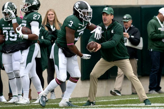 Michigan State's offensive coordinator Dave Warner, right, hands the ball off to LJ Scott during warm ups before the Spartans game against Purdue on Saturday, Oct. 27, 2018, in East Lansing.
