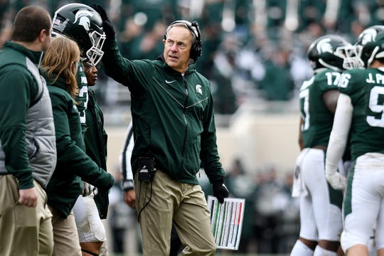 Michigan State's head coach Mark Dantonio pats Joe Bachie on the helmet after he was shaken up on a play during the third quarter on Saturday, Oct. 27, 2018, at Spartan Stadium in East Lansing.
