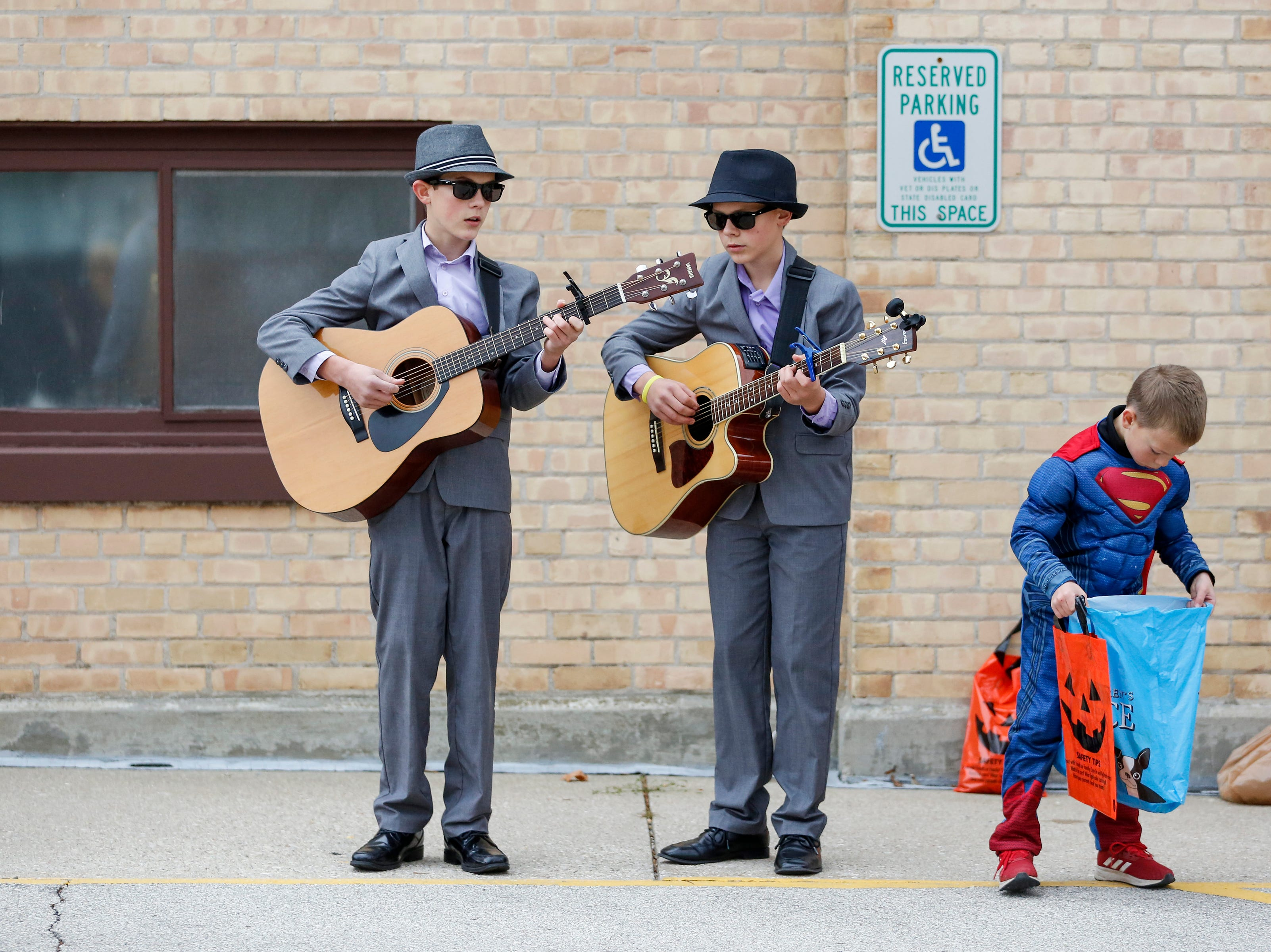 Adam, 13, and Ben, 11, Backus play guitars dressed as the Blues Brothers during the Downtown Trick or Treat event Saturday, October 27, 2018, in Two Rivers, Wis. Joshua Clark/USA TODAY NETWORK-Wisconsin