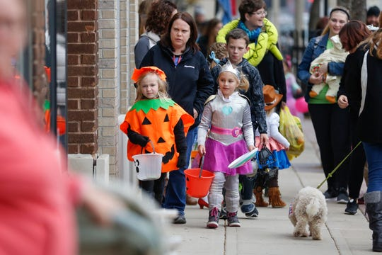 Trick or treaters make their way down Washington Street during Downtown Trick or Treat on Oct. 27, 2018, in Two Rivers, Wis.