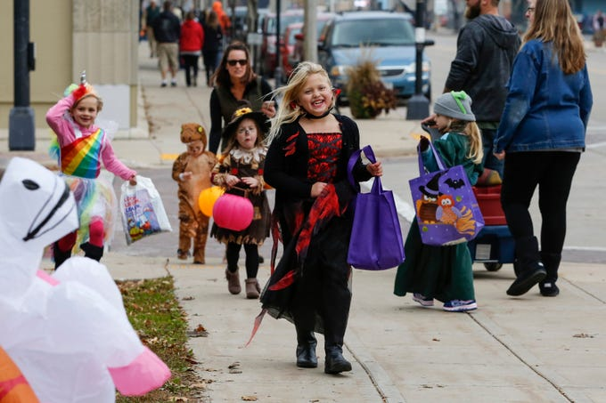 Meadow Grunwald, 8, of New London, happily makes her way from business to business during the Downtown Trick or Treat event on Washington Street Saturday, October 27, 2018, in Two Rivers, Wis. Joshua Clark/USA TODAY NETWORK-Wisconsin