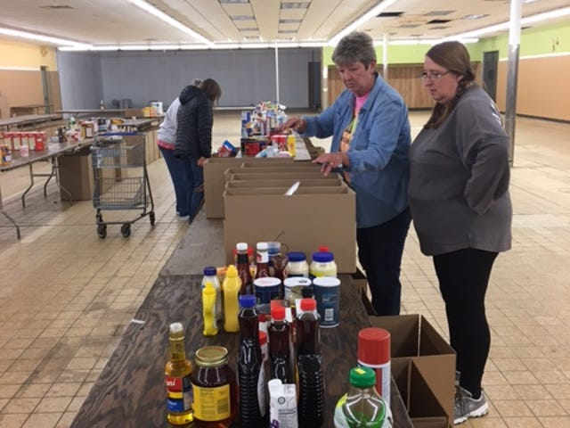 Make a Difference Day volunteers sort and box items at Graham Automall's building at West Fourth Street and Brookwood Way.