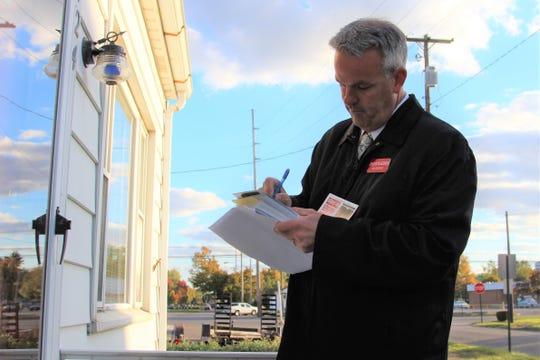 Jason Warner campaigns door to door on Barnhart Street in the race for Marion County judge.