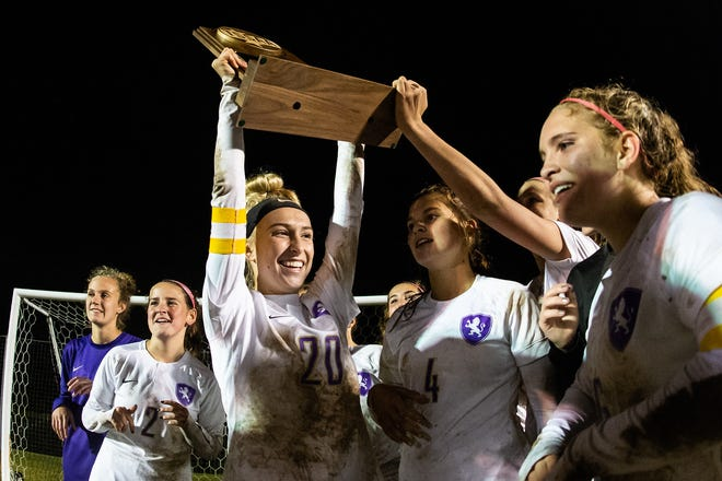 Christ Presbyterian Academy's Cece Pascarella (20) holds up the state championship trophy after winning the Division II-A girls' soccer final against Chattanooga Christian School at Richard Siegel Soccer Complex on Friday, Oct. 26.